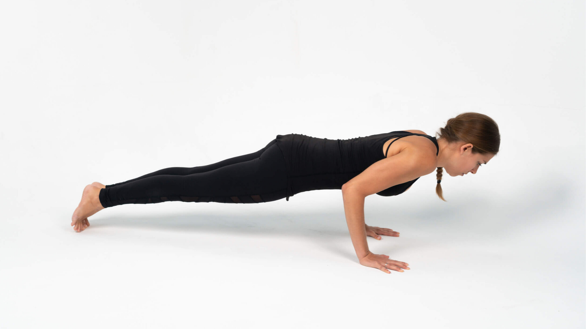 Woman practicing yoga chaturanga dandasana.