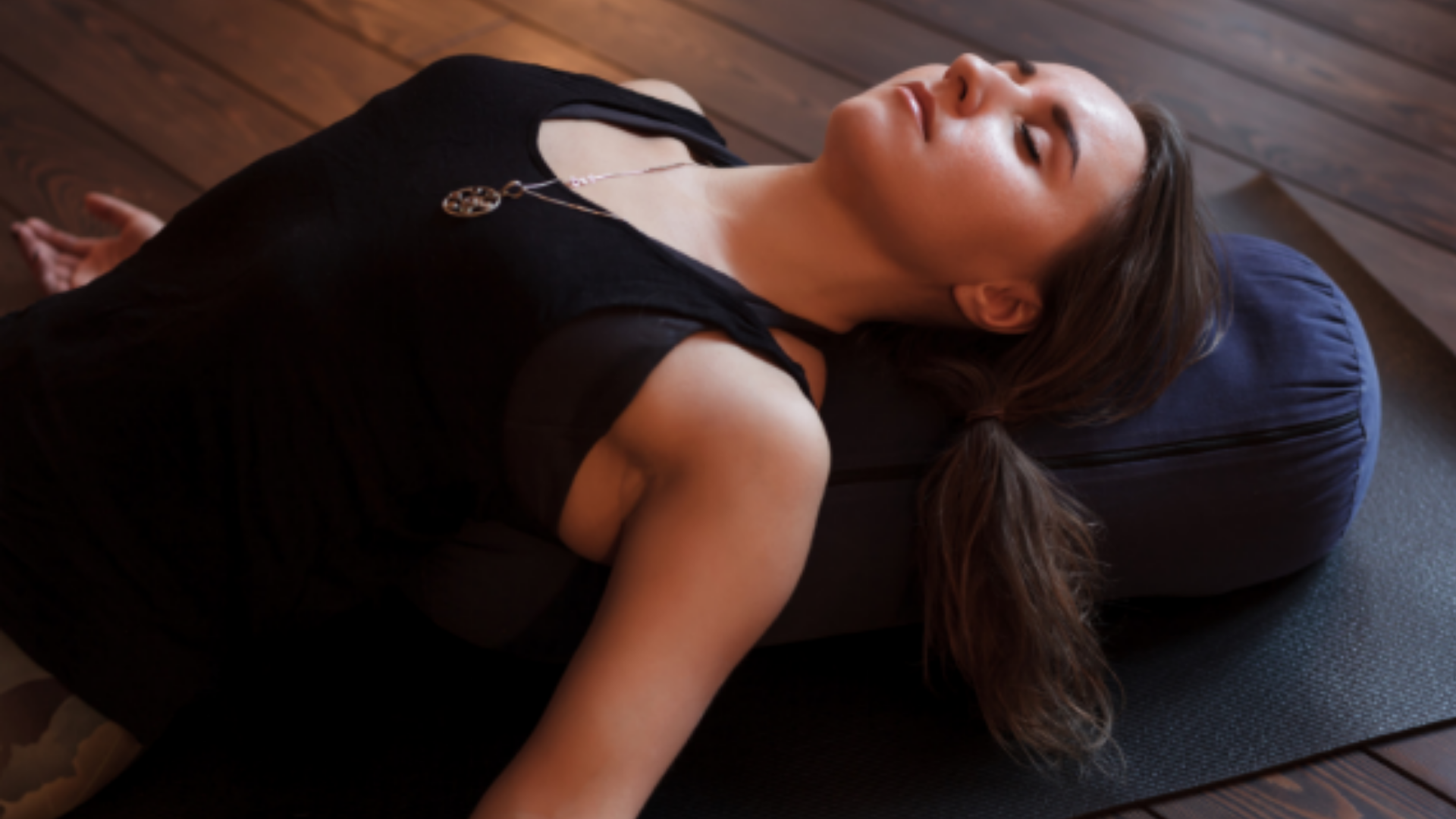 Woman resting with her back supported by a yoga bolster