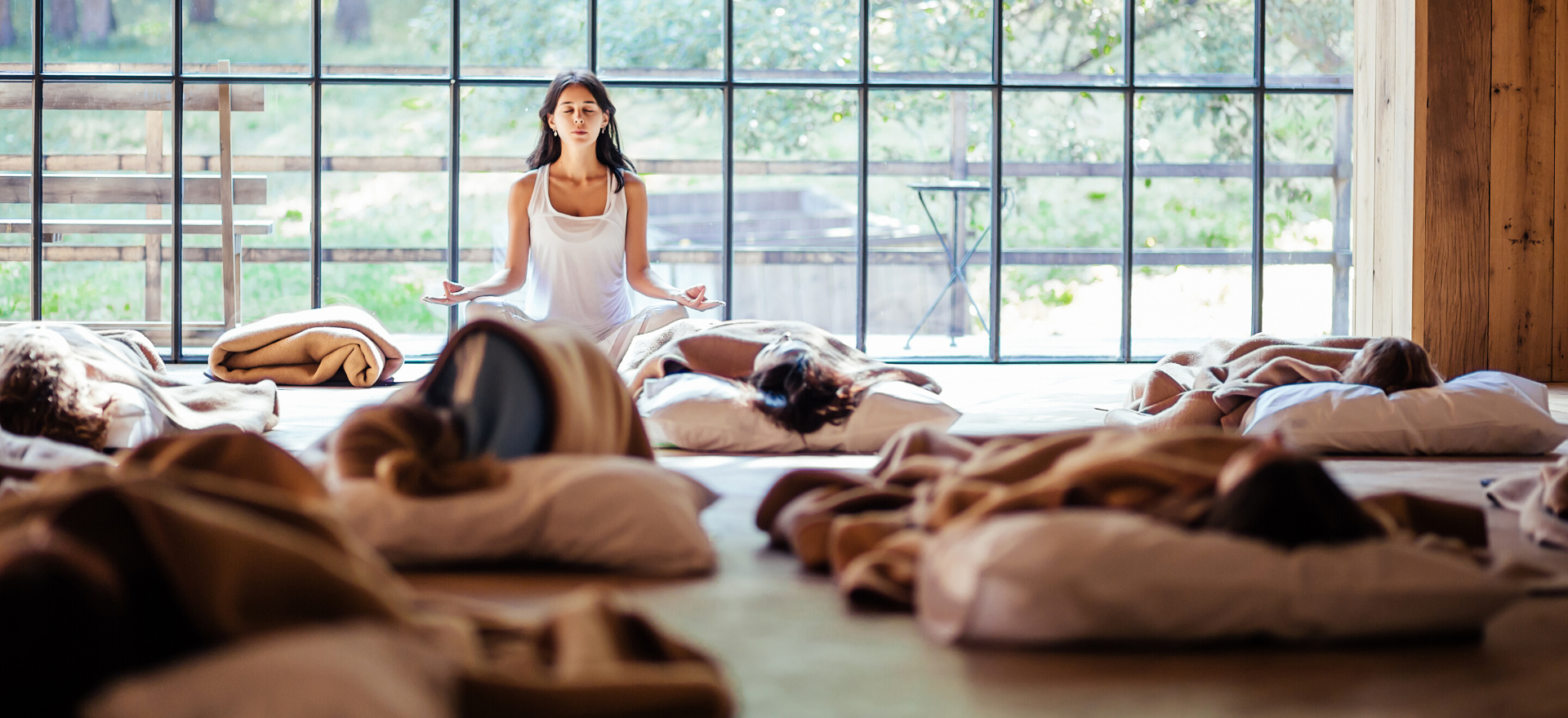 Yoga instructor meditates during her yoga class while students rest in savasana.
