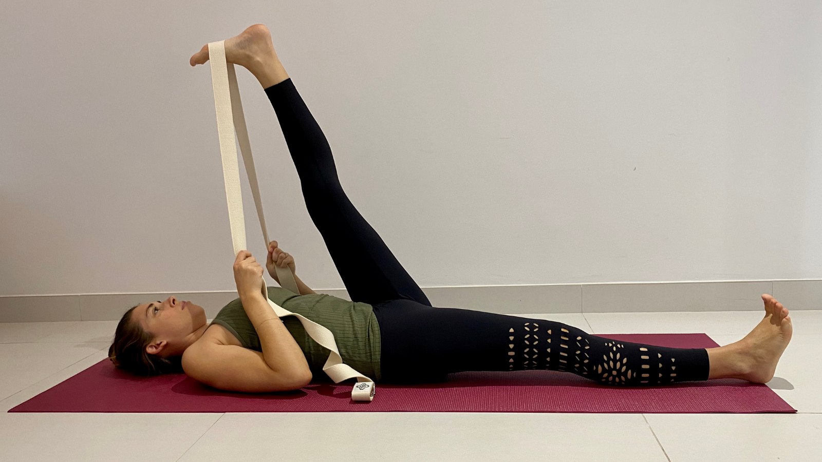 Yoga beginner tips to lengthen the hamstrings and relieve back pain in Reclined Big Toe Pose (Supta Padangusthasana)