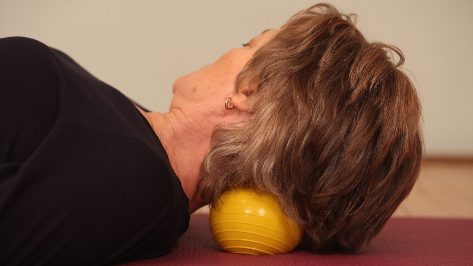 How to use a rubber exercise ball right under your neck to release pain and neck tension