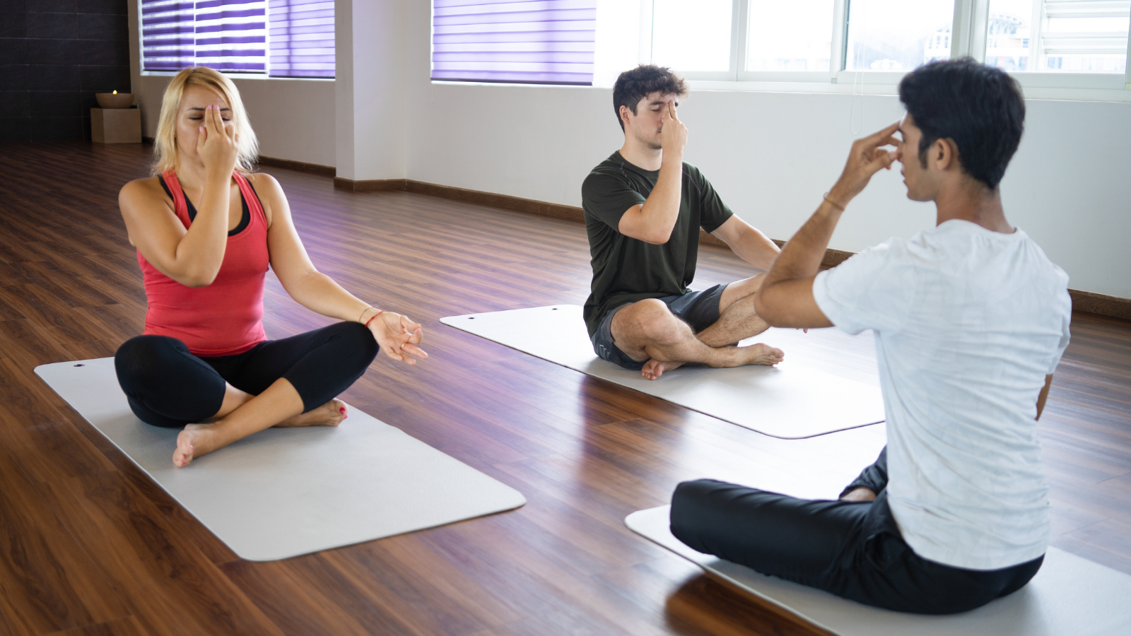 Students practicing alternate nostril breathing technique with instructor at yoga class