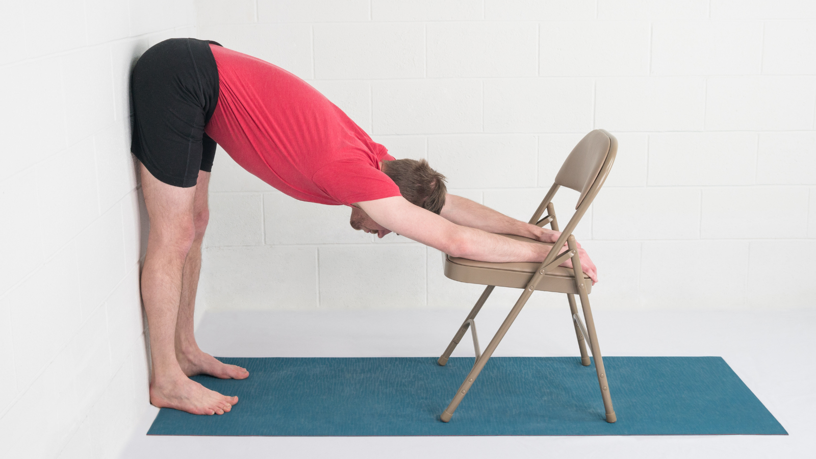 Man practicing Uttanasana (Standing Forward Bend Pose) variation with chair at the wall