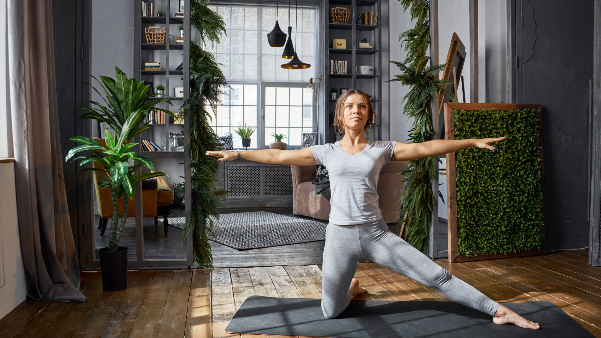 Woman practicing yoga gate pose at home.