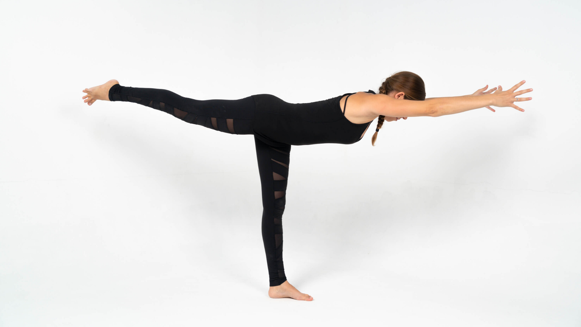 Woman practicing yoga warrior III pose virabhadrasana III.