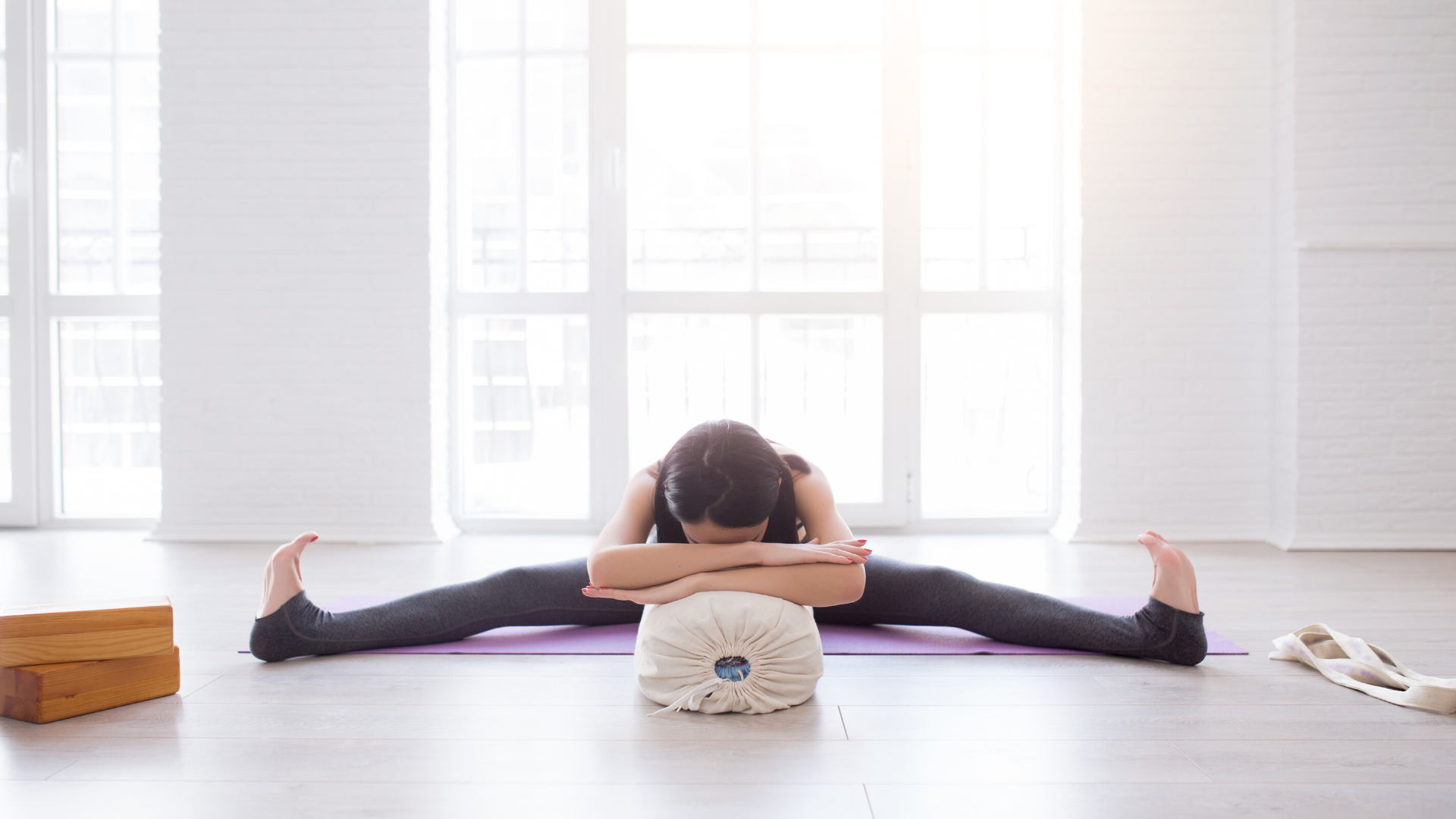 Woman practicing yoga supported wide leg forward bend.
