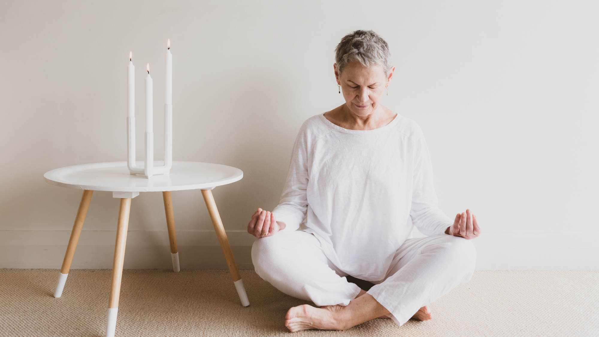 Woman practicing meditation with candles.
