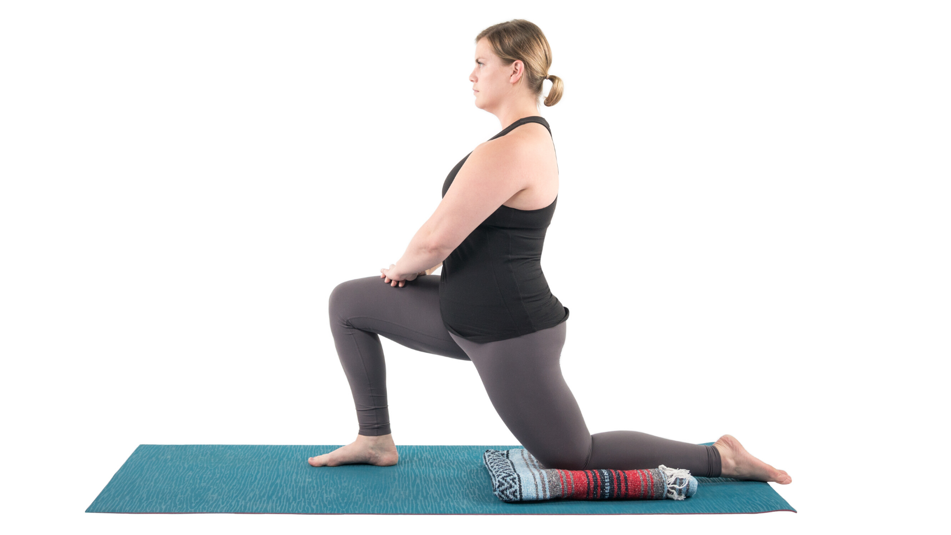 Woman practicing anjaneyasana yoga lunge pose.