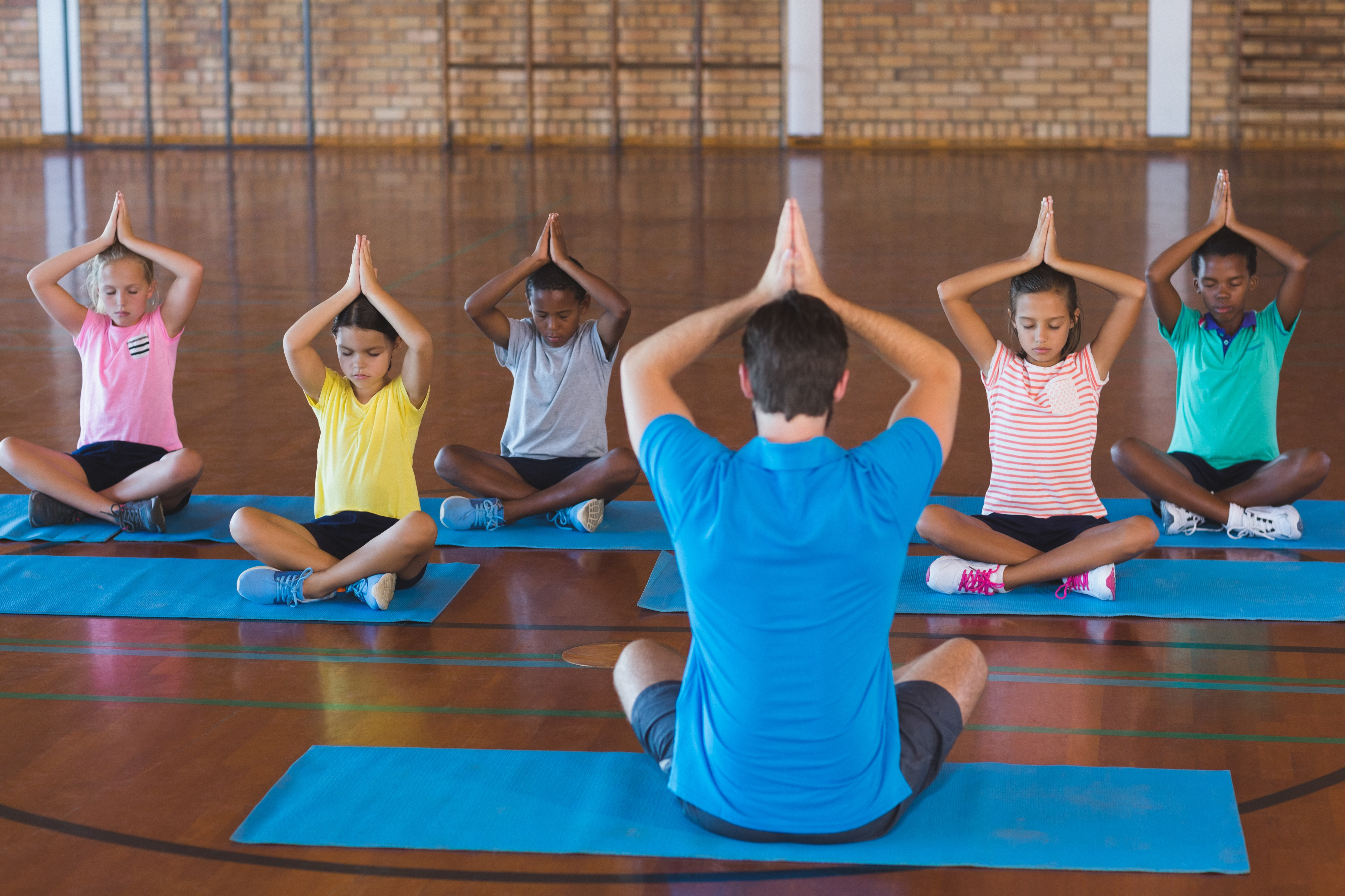 kids practicing yoga at school with teacher to reduce stress and anxiety and develop social skills