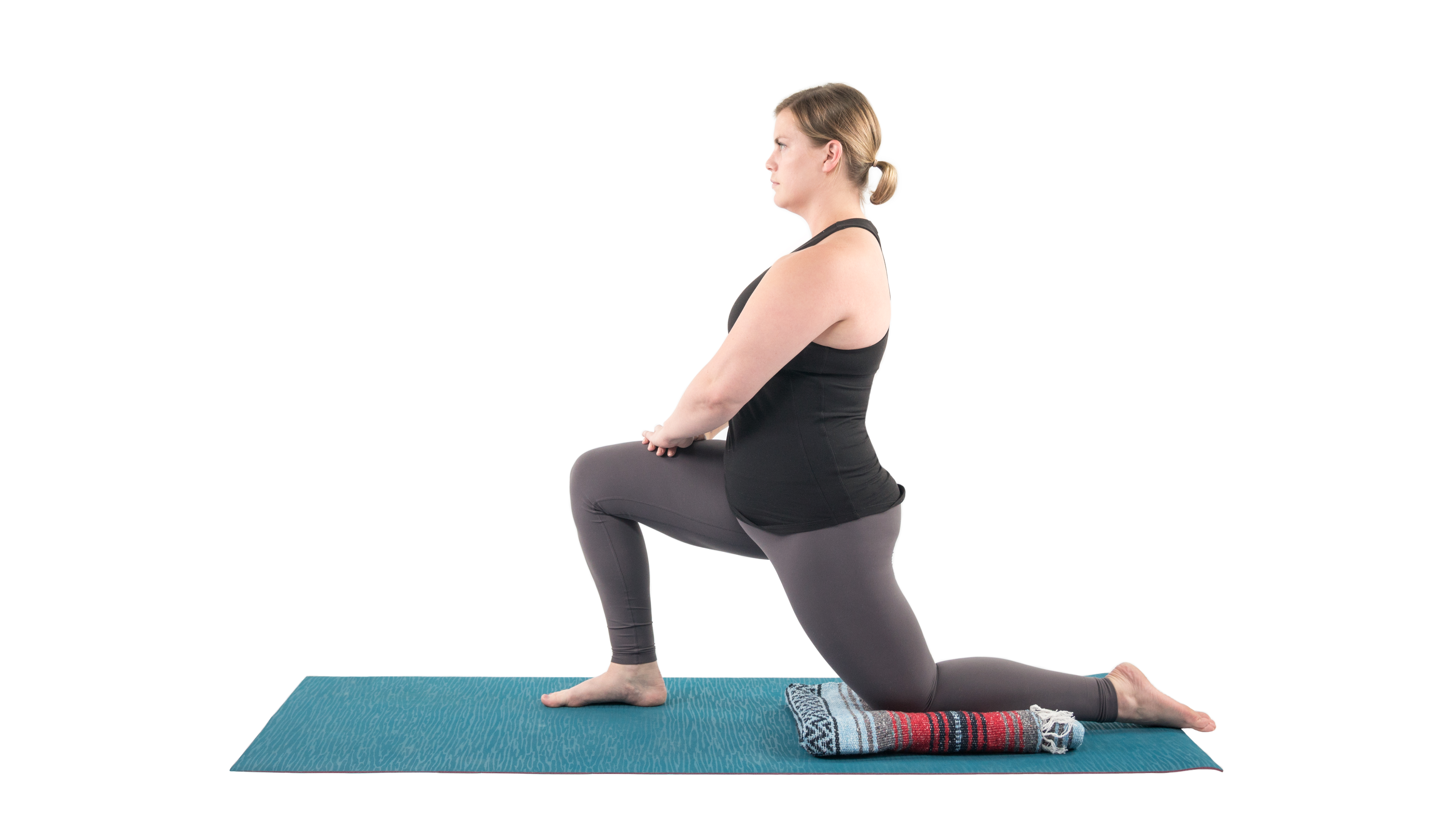 Woman in the low lunge quad stretch yoga pose in preparation for the Dancer Pose (Natarajasana)