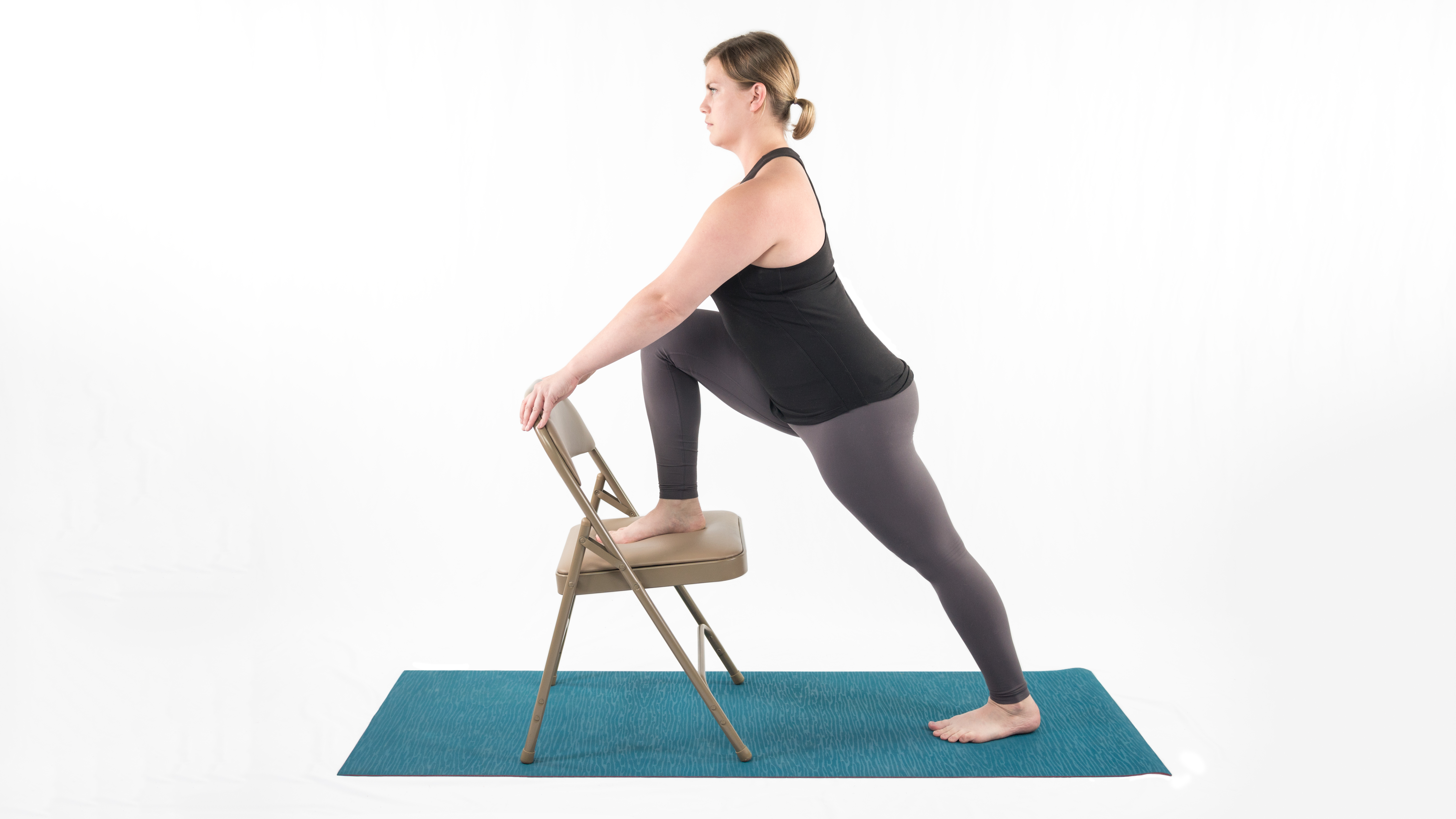 A woman in Lunge with Chair, which stretches the leg muscles in preparation for Warrior 2 yoga pose