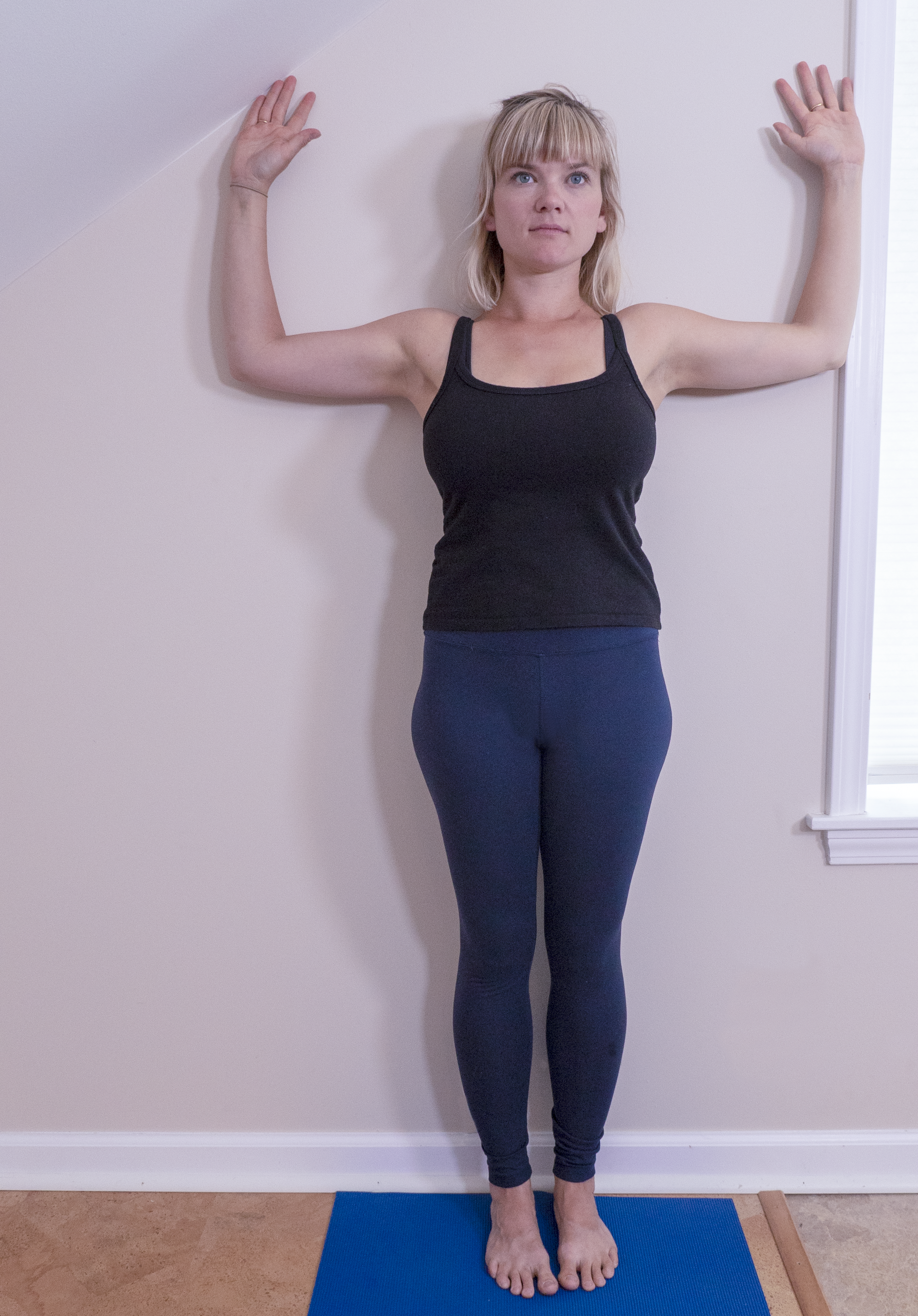woman practicing cactus arms in yoga at the wall