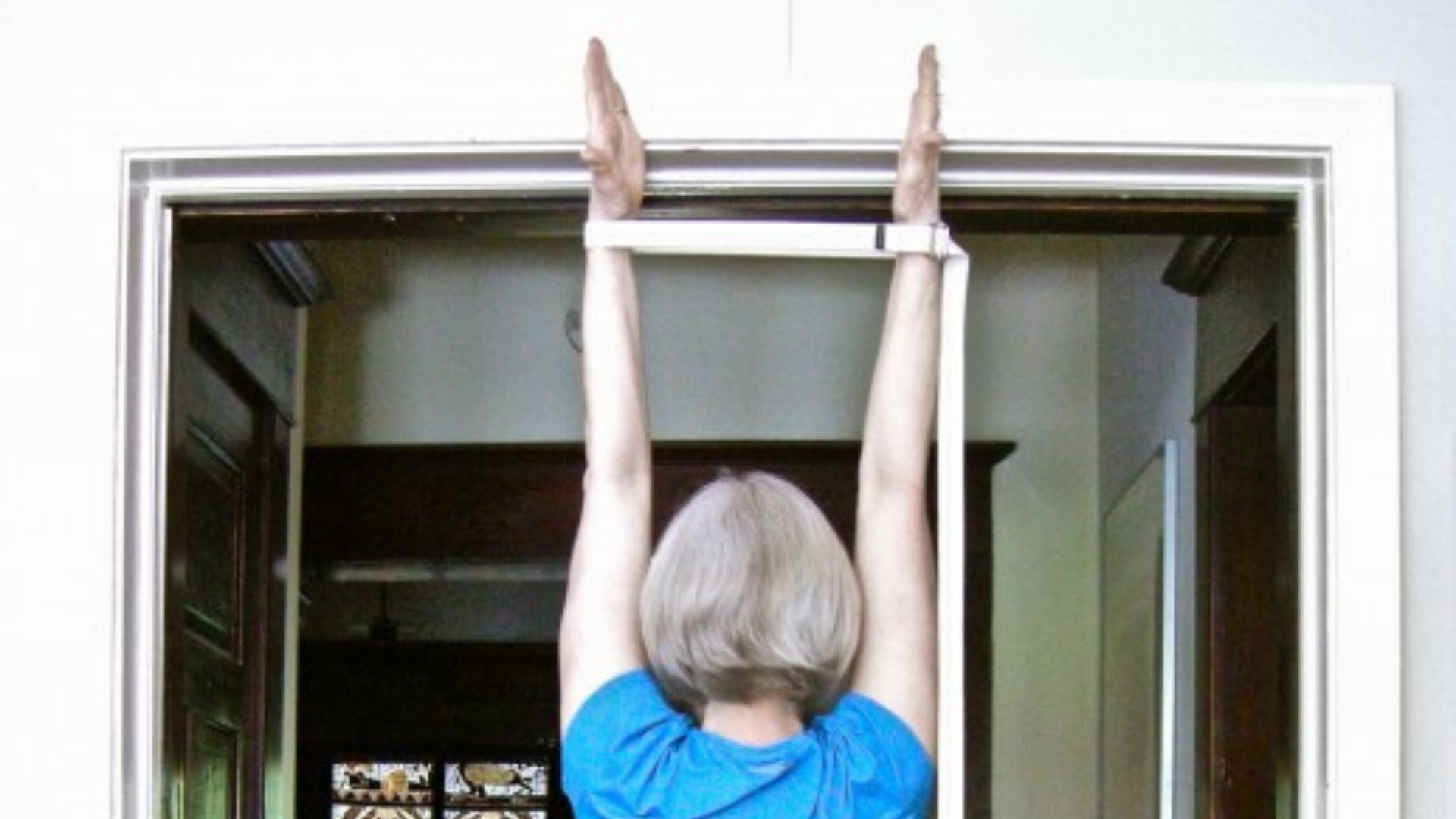 Woman stretching arms overhead with hands pressing into top door jamb