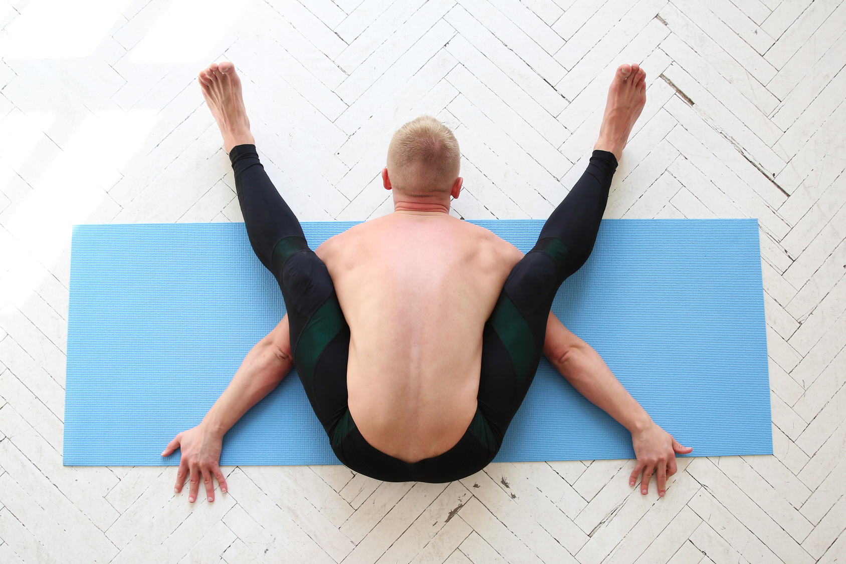 Man doing Tortoise Pose (Kurmasana) as part of the discussion of male vs. female flexibility in yoga