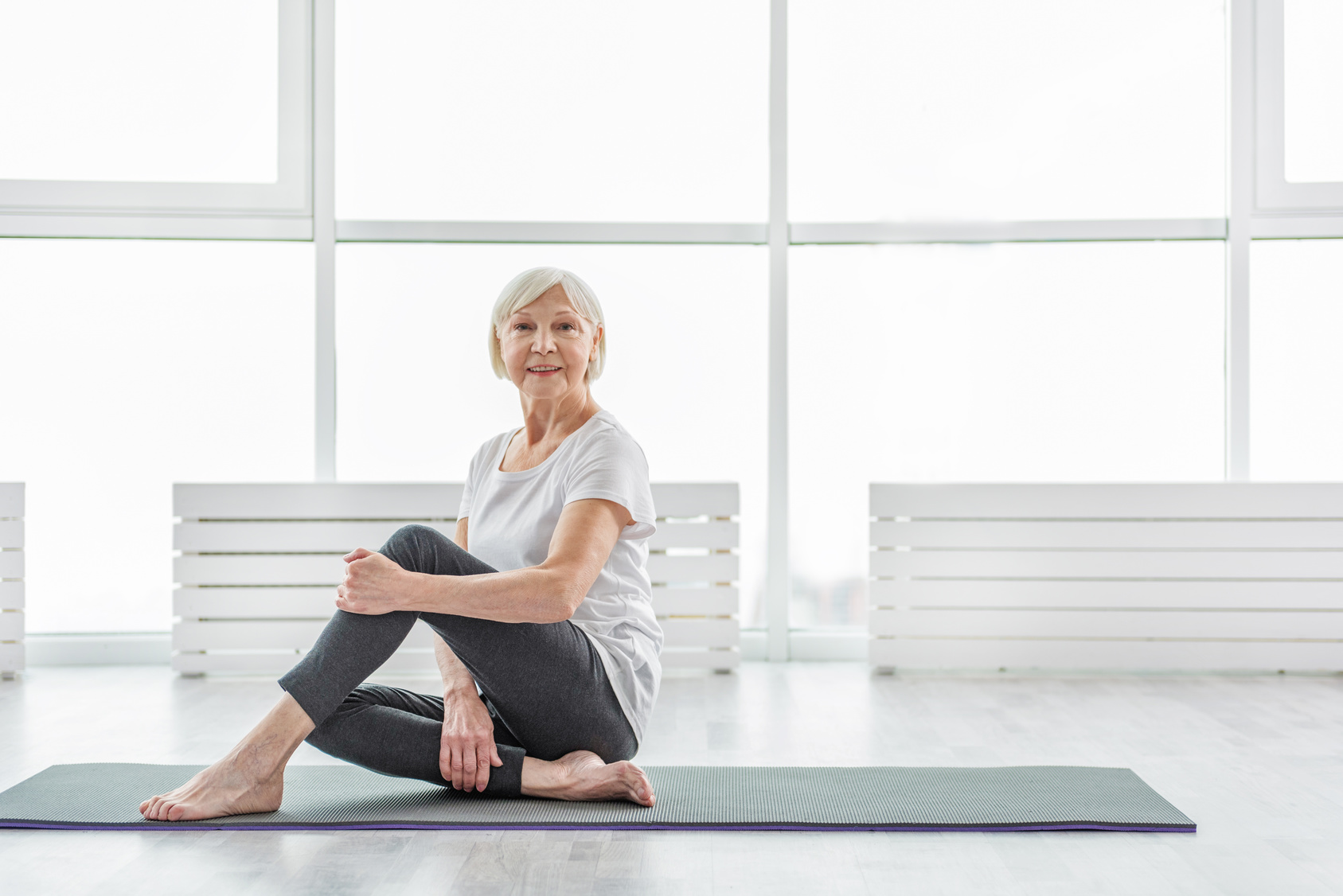 Older woman practicing yoga for health benefits recovering from stroke