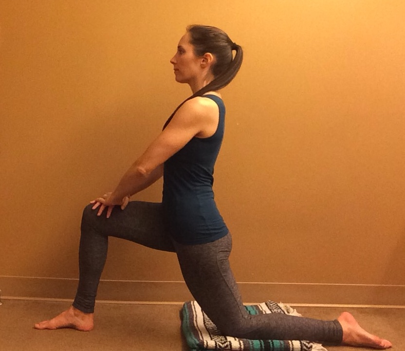 A woman doing Low Lunge (Anjaneyasana), a yoga pose to stretch the psoas muscle