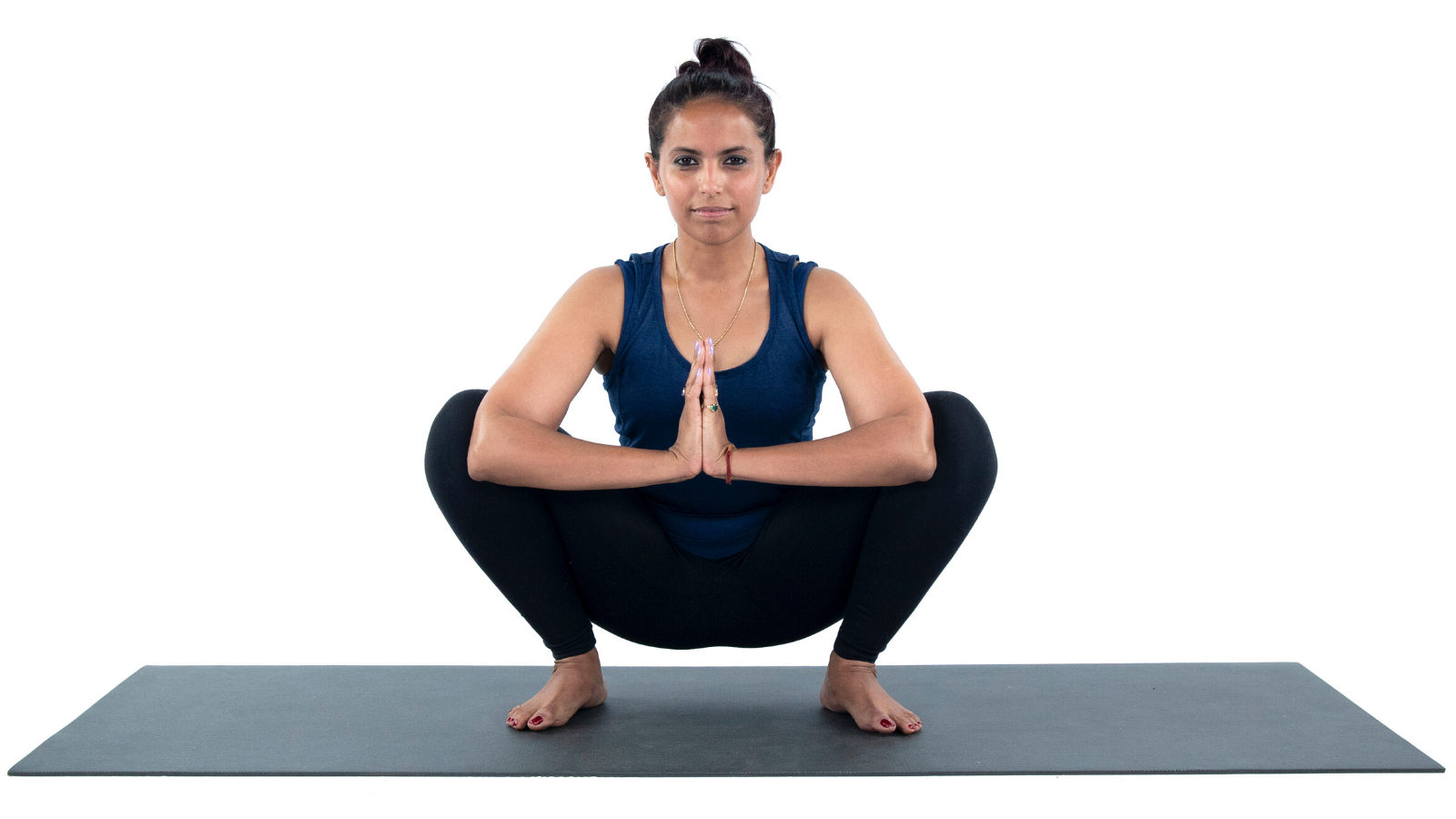 Woman practicing yoga Garland Pose
