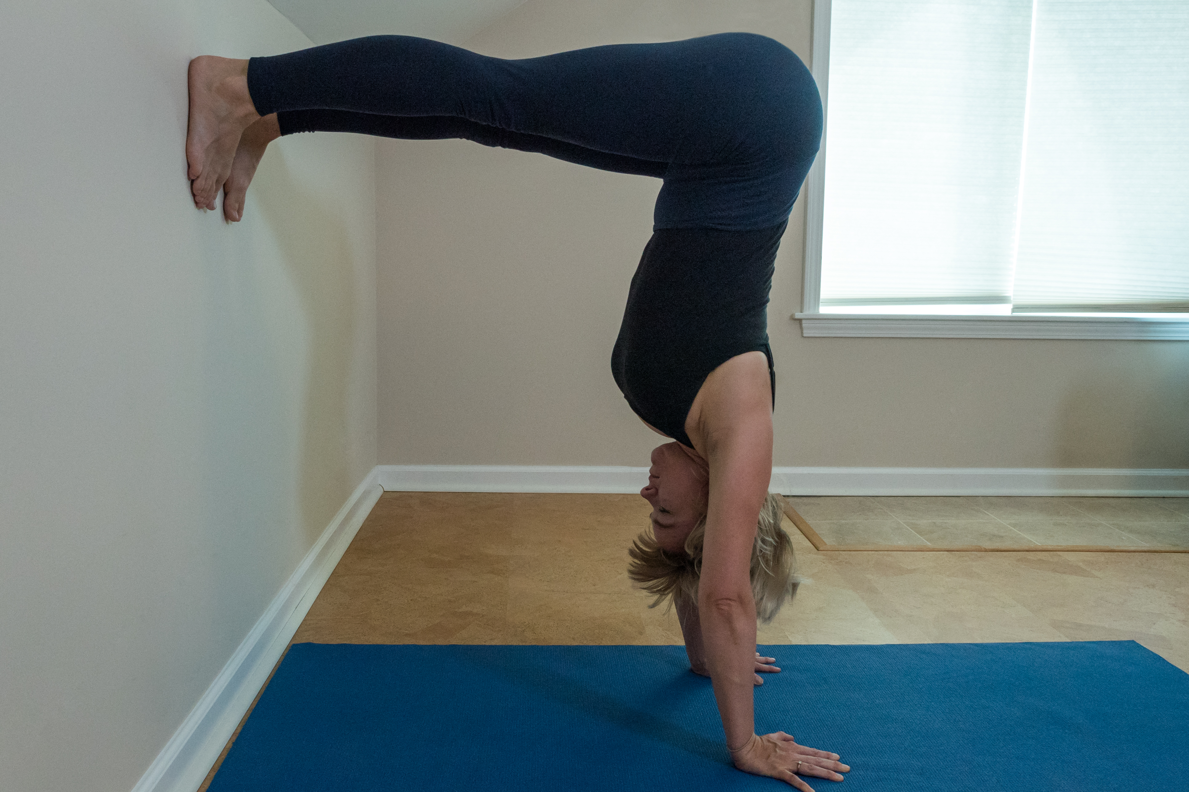 woman practicing half handstand at the wall L-position