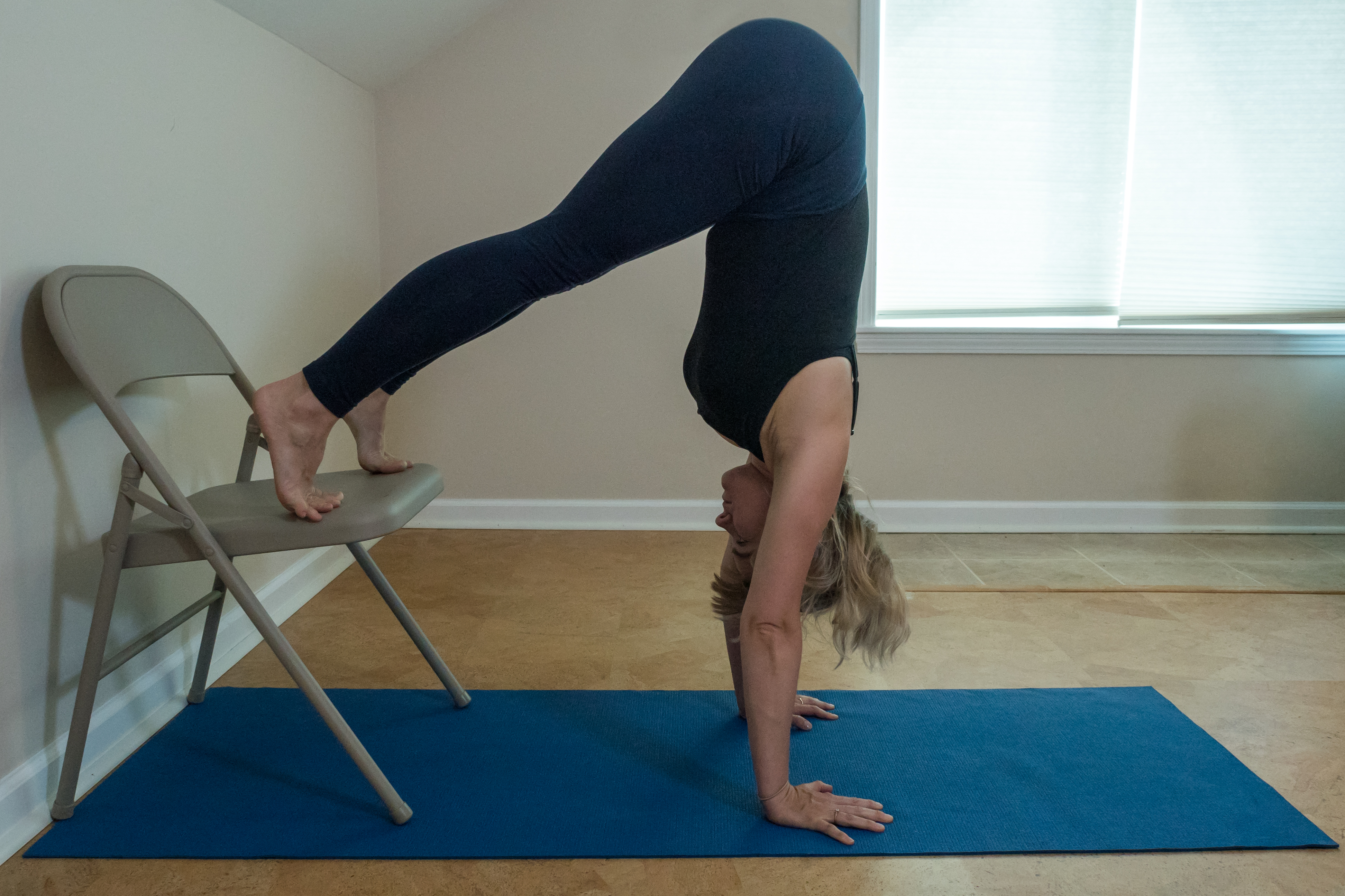 woman preparing for handstand with L-handstand feet on a chair