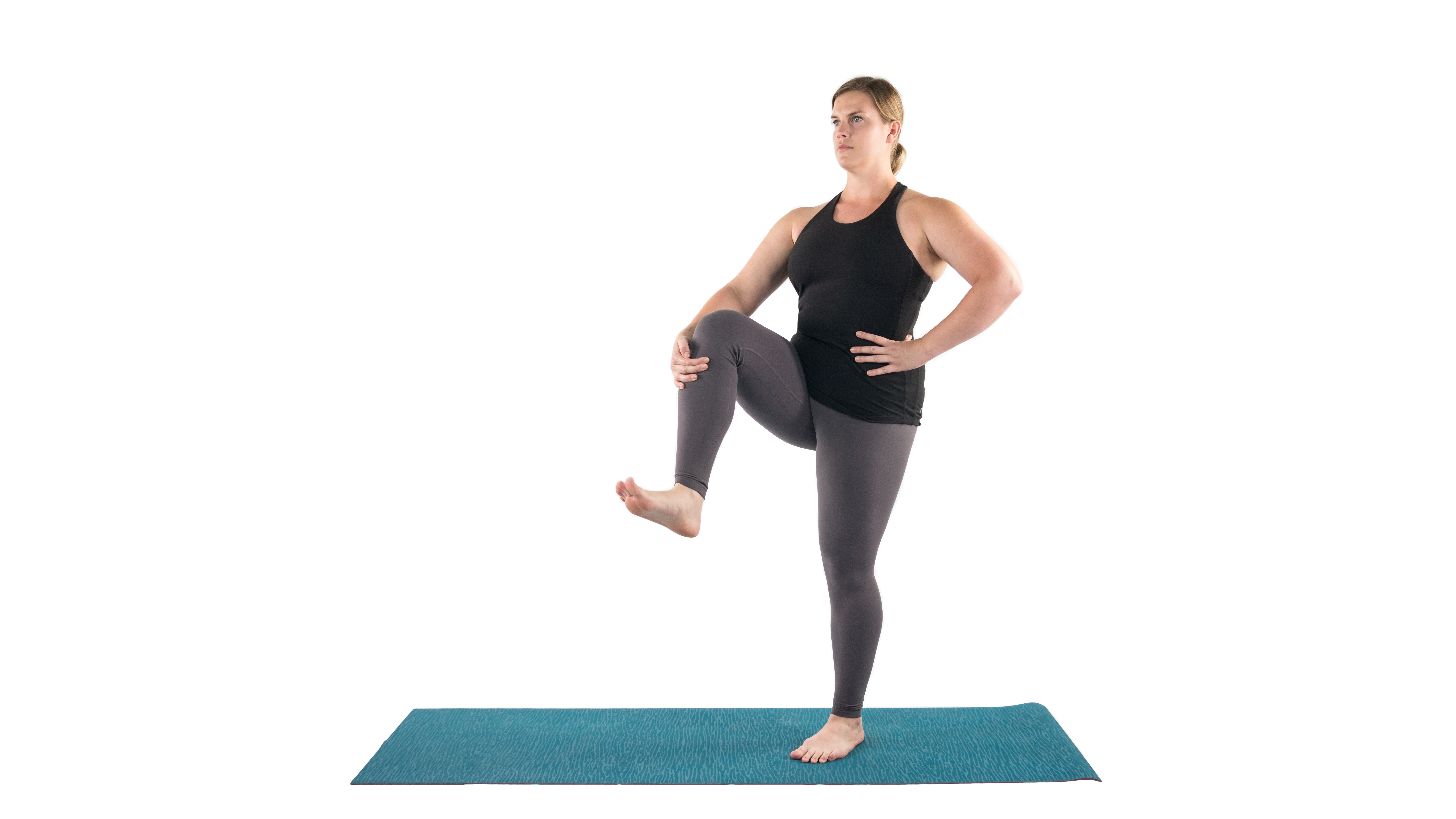 Woman in a simple standing balance yoga pose to stretch muscles in preparation for Dancer Pose
