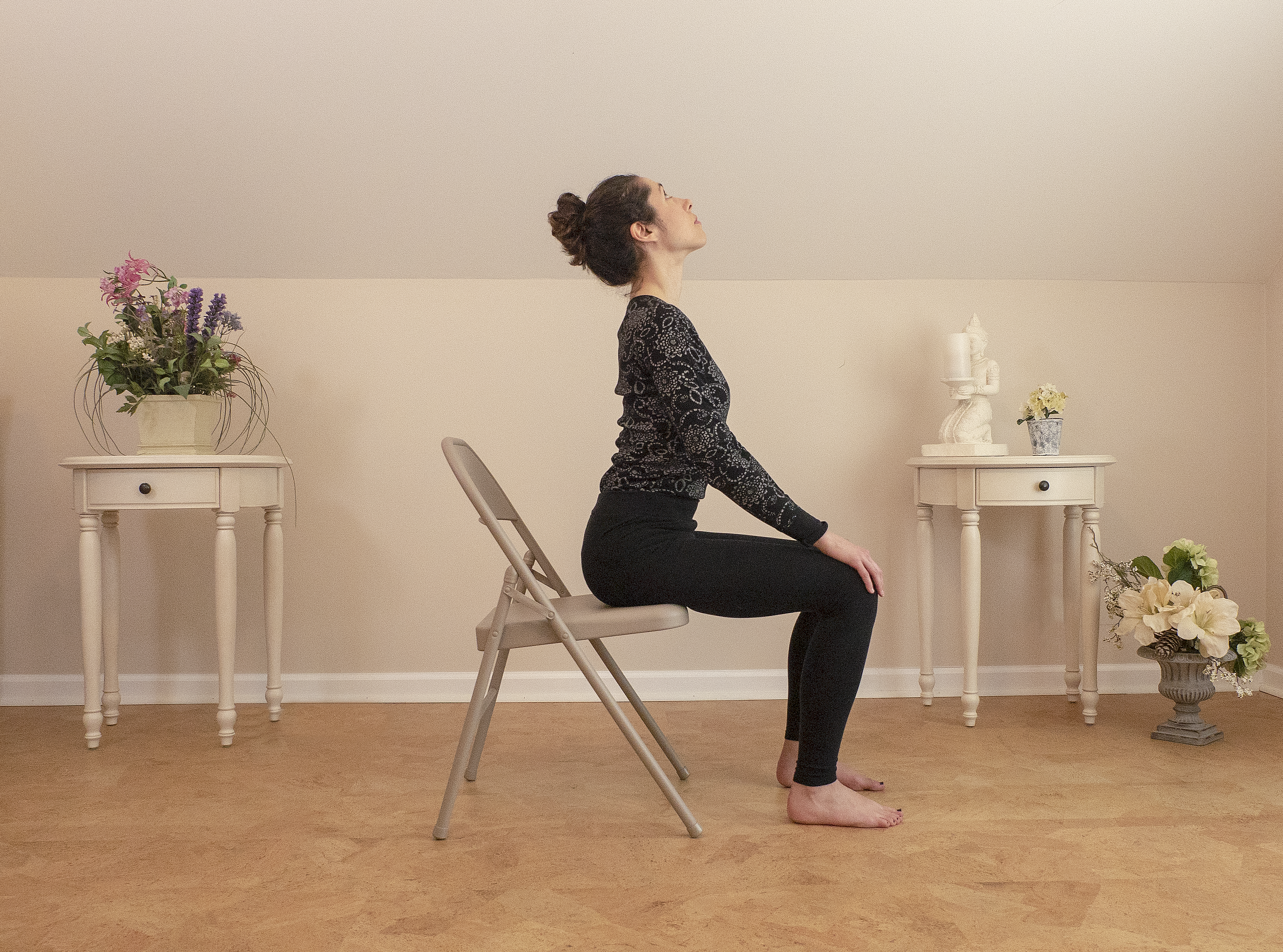 woman practicing cow pose (Bitilasana) yoga in a chair