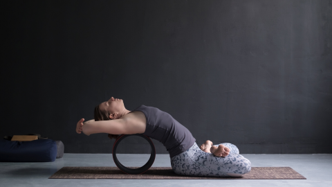Woman practicing supported fish pose with yoga wheel.
