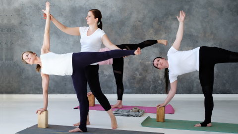 Yoga teacher assisting student with Half Moon Pose.