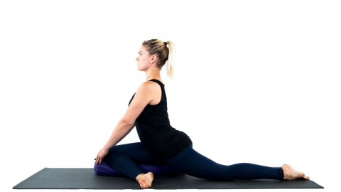 Yoga woman in pigeon pose with blanket