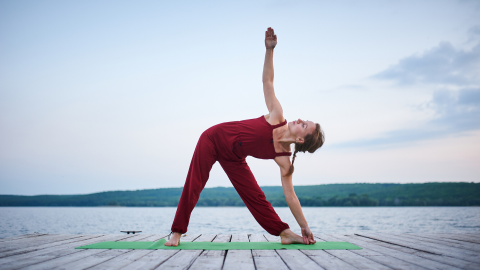 Woman practicing yoga triangle pose on a dock.