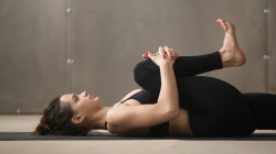 woman practicing yoga, stretching in Knees to Chest (Apanasana) which is good for digestion