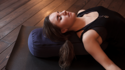 Woman resting after a yoga class in Corpse Pose or Savasana with bolster for spine comfort