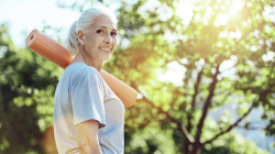 Lovely smiling mature woman looking calm while carrying her yoga mat