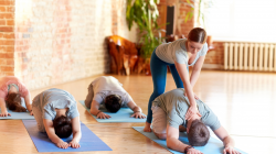 Yoga instructor working with with yoga students to offer quality instruction