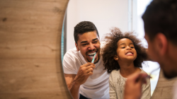 Father and daughter happily brushing teeth together in the mirror.