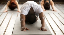 Male yoga student practicing balasana childs pose