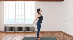 Woman practicing yoga standing chest opening stretch.