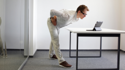 Man performing easy yoga back stretch in workplace