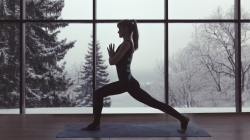 Woman practicing yoga in front of large window in winter.