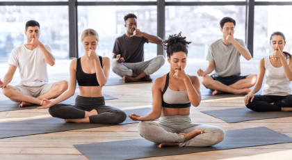 Yoga students in class practicing healthy breathing through pranayama exercise