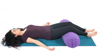 Restorative Savasana with a bolster to support the legs