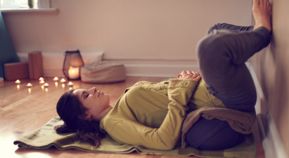 Serene lady relaxing and meditating for digestive health on a yoga mat in a cozy house
