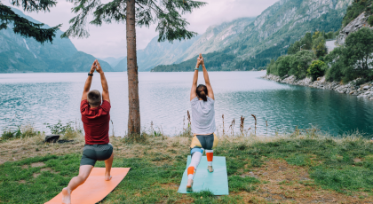 Fitness lifestyle concept - sportive couple making yoga exercises sitting on mats outdoors near lake