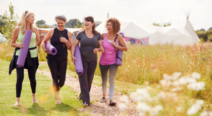 Group Of Mature Female Friends On Outdoor Yoga Retreat Walking Along Path Through Campsite.