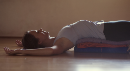 Woman practicing yoga for sleep in Fish Pose (Matsyasana)