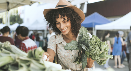 Yoga student buying vegetables at the farmers market.