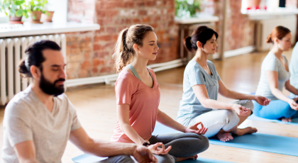 Group of yoga students practicing meditation in class.