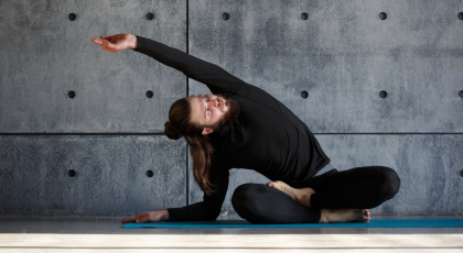 Male yoga student stretching to the side in yoga class.