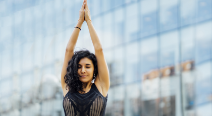 Woman practicing yoga outside hands in prayer.