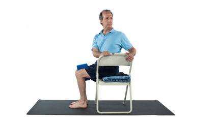 Older man practicing chair yoga twist with block between thighs sitting in chair
