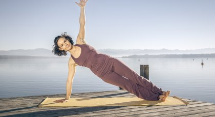 woman practicing Vasisthasana (Side Plank Pose) yoga alignment by the water